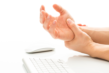 Working too much - suffering from a Carpal tunnel syndrome - young man holding his wrist in pain due to prolonged use of keyboard and mouse over white background (color toned image; shallow DOF)